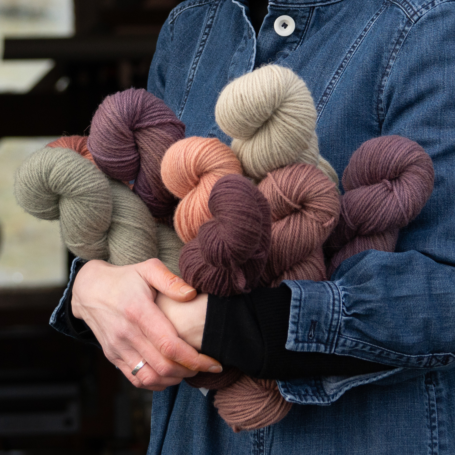 Photo of an adult in a denim shirt holding a stack of skeins of yarn