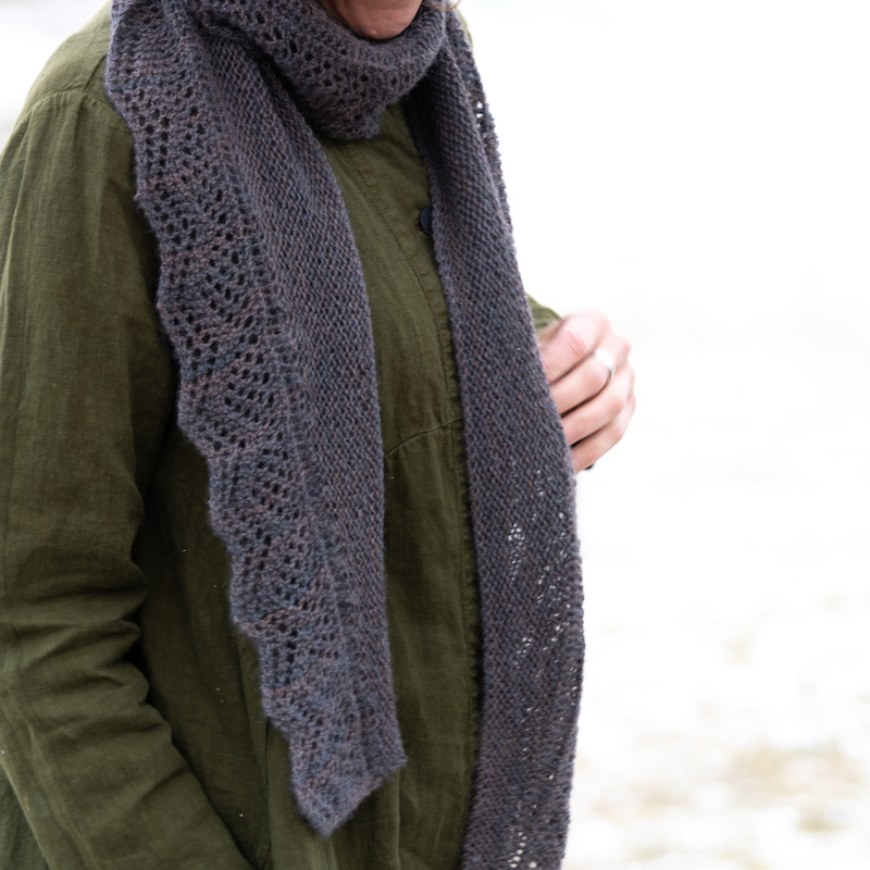 Photo of an adult wearing a green linen shirt and greyish purple knitted shawl
