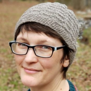 Photo of a woman smiling to camera. She has glasses and is wearing a knitted hat.