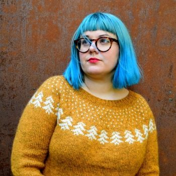 Karie Westermann wearing glasses and her Vinterskov design - a egg-yolk yellow jumper with white tree motif around the yoke.
