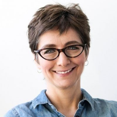 Photo of Kate Atherley. She is wearing a blue shirt and striking dark-framed glasses, and smiling at the camera.