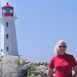 Photo of Luise O'Neill wearing sunglasses and standing in front of a lighthouse on a bright sunny day.