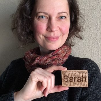 Photo of a woman holding up a badge with Sarah against a background of knitting stitches