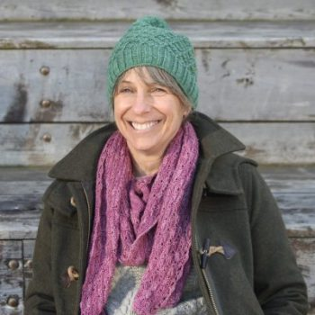Photo of Thea Colman sitting infront of a wooden building, wearing a knitted hat and scarf