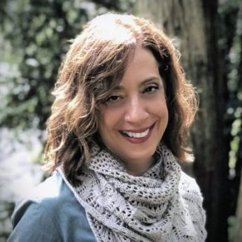 Photo of a woman smiling to the camera, wearing a lace knitted shawl. She is outdoors and there are trees in the background.