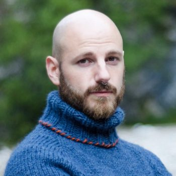 Photo of a man wearing a blue knitted jumper with high rolled neck. He looks towards the camera with a somewhat curious expression.