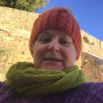 Cathy is wearing an orange hat, purple cabled sweater and lime green scarf and stand before an old stone wall