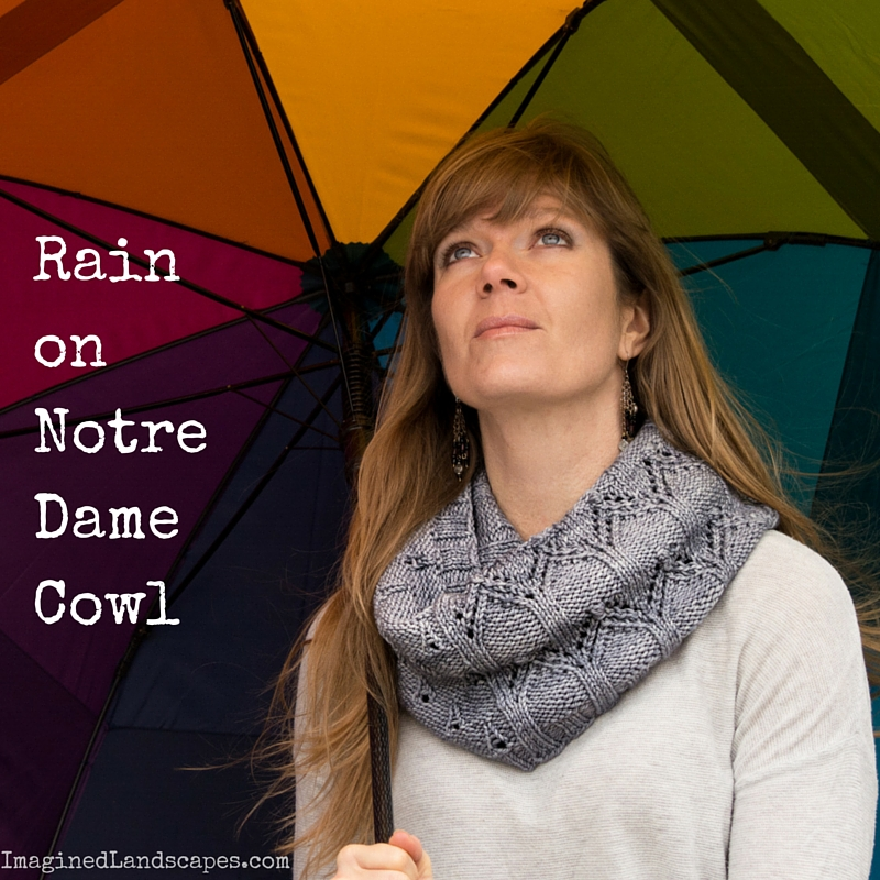 photo of Sarah wearing grey lace cowl and standing under a rainbow coloured umbrella